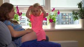 La belle femme enceinte et sa fille mignonne de fille attendent la naissance de fils de frère banque de vidéos