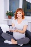 La belle femme enceinte prépare des articles d'habillement pour le nouveau-né Images libres de droits