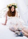 La belle femme enceinte rousse se trouve sur un lit à la maison grossesse, les gens et concept d'attente photographie stock libre de droits