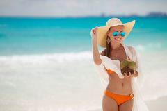 La belle femme enlève la soif avec du lait de noix de coco Photo stock