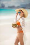 La belle femme enlève la soif avec du lait de noix de coco Photographie stock libre de droits