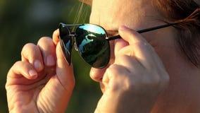 La belle femme enlève ses lunettes de soleil dehors au coucher du soleil banque de vidéos