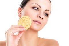 La belle femme enlève l'éponge de maquillage pour le visage Image libre de droits