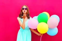 La belle femme est envoie à des prises d'un baiser d'air un air les ballons colorés sur le fond rose images stock