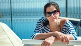 La belle femme européenne dans des lunettes de soleil se trouvant sur la chaise de plate-forme avec des bras a croisé apprécier l banque de vidéos