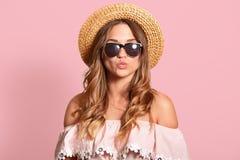 La belle femme faisant le geste de baiser, maintient des lèvres équipement de port femelle arrondi et attrayant d'été et lunettes images libres de droits