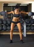 La belle femme fait des exercices avec le bar images stock