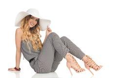La belle femme gaie dans la salopette, le chapeau de Sun et des talons hauts s'assied sur le plancher photos stock