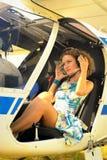 La belle femme habillent dedans le pilote dans un habitacle de l'avion ultra-léger Photos libres de droits
