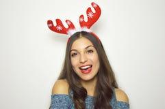 La belle femme heureuse avec des klaxons de renne sur sa tête regarde l'appareil-photo sur le fond blanc Vacances de Noël Photo stock