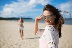 La belle femme heureuse dans des lunettes de soleil se tenant sur la plage avec frien Image libre de droits
