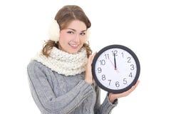 La belle femme heureuse en hiver vêtx tenir l'OIN d'horloge de bureau Photographie stock