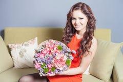 La belle femme heureuse a reçu un bouquet de fleur des tulipes Images stock