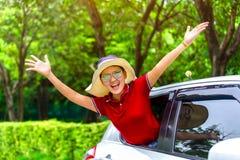 La belle femme heureuse voyageant en une voiture détendent pendant les vacances su Photographie stock