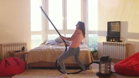 La belle femme hoovering le plancher à la maison utilisant l'aspirateur moderne et écoute la musique et la danse housework banque de vidéos