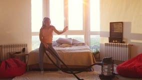 La belle femme hoovering le plancher ? la maison utilisant l'aspirateur moderne et ?coute la musique avec des ?couteurs clips vidéos