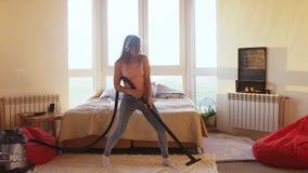 La belle femme hoovering le plancher ? la maison utilisant l'aspirateur moderne et ?coute la musique avec des ?couteurs banque de vidéos