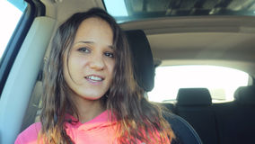 La belle femme joyeuse dans le sourire de voiture chante Image libre de droits