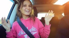 La belle femme joyeuse dans le sourire de voiture chante et danse Images stock