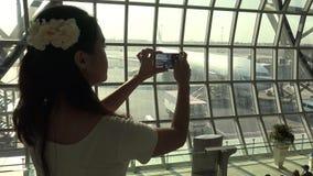 la belle femme 4k asiatique prennent la photo avec le téléphone à l'avion dans l'aéroport clips vidéos