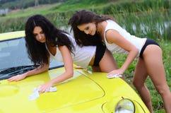 La belle femme lave la voiture Photographie stock