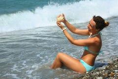 La belle femme lave le seashell en mer images stock