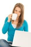La belle femme lit des actualités à l'ordinateur portable Photos libres de droits