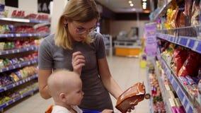 La belle femme lit le contenu de produit sur le paquet des biscuits, alors que son petit bébé s'assied dans une épicerie clips vidéos