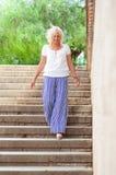 La belle femme mûre marche en bas des étapes, souriant et avec la Floride photos libres de droits