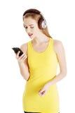 La belle femme occasionnelle dans le dessus jaune écoute la musique. Photographie stock libre de droits