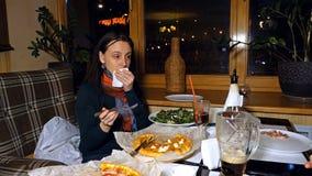 La belle femme parle à un ami dans un restaurant Image stock