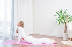 La belle femme pratique le yoga à la maison sur le tapis de yoga, faisant l'exercice de cobra, pose de Bhujangasana photographie stock
