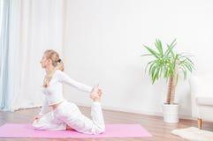 La belle femme pratique le yoga à la maison sur le tapis de yoga, fille faisant la pose d'Eka Pada Rajakapotasana images stock
