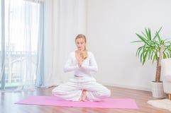 La belle femme pratique le yoga à la maison sur le tapis de yoga images stock