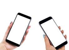 La belle femme remet tenir deux téléphone intelligent avec l'écran blanc d'isolement Lieu de travail d'affaires avec l'espace de  Photos libres de droits