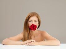 La belle femme retenant le rouge s'est levée dans la bouche Image libre de droits