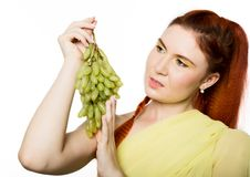La belle femme rousse lèche des raisins Concept de la consommation saine image stock