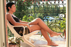 La belle femme s'assied sur le balcon Photo libre de droits