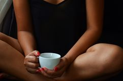 La belle femme s'assied sur le sofa, elle tient une tasse de café dans des ses mains photo stock