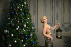 La belle femme s'est habillée dans l'arbre de Noël près décoré sexuel de lanterne de sorcière de robe de soirée Photos stock