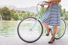 La belle femme s'est habillée dans le voyage de robe de mode en la bicyclette de vintage Photo stock