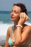 La belle femme s'est penchée la cuvette de seashell à une oreille images stock