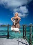 La belle femme saute sur une plate-forme en bois au-dessus de la mer Photos libres de droits