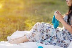 La belle femme se penchant contre un arbre tricote Photos stock