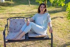La belle femme se repose sur un banc en parc images libres de droits