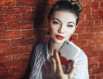 La belle femme se tenant devant le mur de briques et font le selfie Avec les lèvres rouges Téléphone unfocused Image libre de droits
