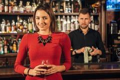 La belle femme se tient près du cocktail de barre Image stock