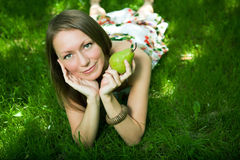 La belle femme se trouve sur l'herbe photo stock