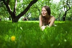 La belle femme se trouve sur l'herbe Photographie stock