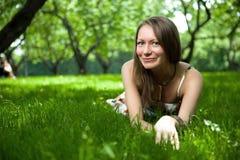 La belle femme se trouve sur l'herbe Photos stock
